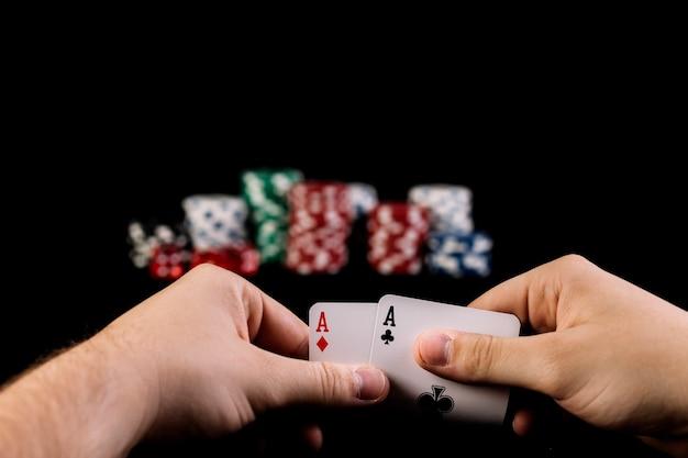 La mano dell'uomo che tiene due carte da gioco degli assi