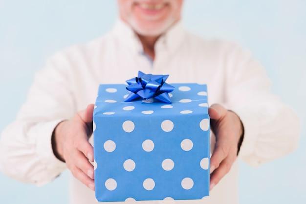La mano dell'uomo che tiene il contenitore di regalo di compleanno avvolto blu