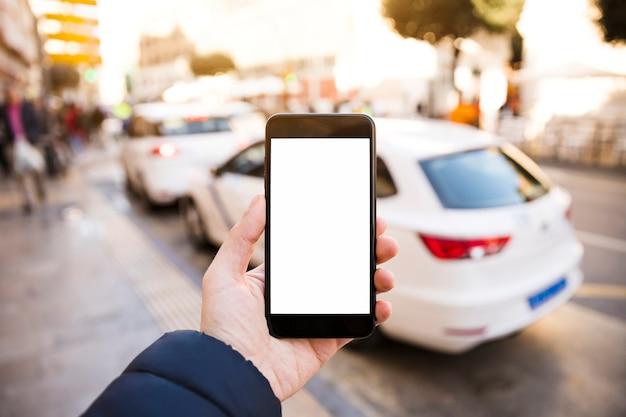 La mano dell'uomo che tiene il telefono cellulare davanti al traffico sulla strada