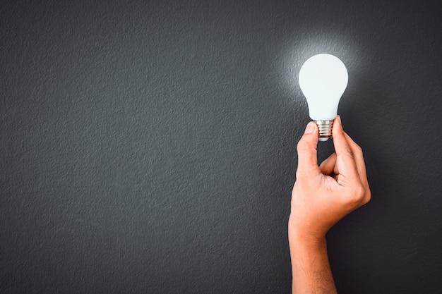 La mano dell'uomo che tiene la lampadina del led sopra il fondo nero della parete di colore