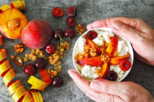 La mano dell'uomo che tiene un cucchiaio sopra una ciotola con formaggio e frutta. fiocchi di latte. nastro di misurazione. il concetto di una dieta sana. fiocchi di latte. probiotici. latticini fermentati.