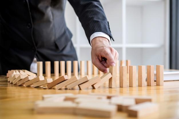 La mano dell'uomo d'affari che ferma l'effetto di legno di domino di caduta dal continuo ha rovesciato o rischia