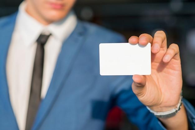 La mano dell'uomo d'affari che mostra carta bianca in bianco