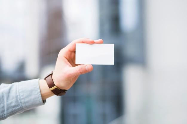 La mano dell'uomo d'affari che mostra il biglietto da visita in bianco bianco