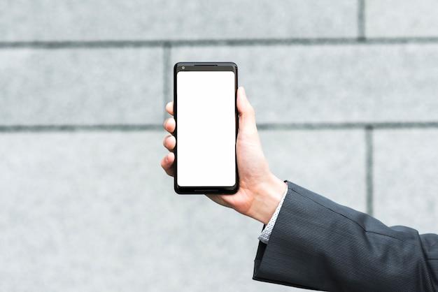La mano dell'uomo d'affari che mostra lo schermo mobile in bianco contro il contesto vago