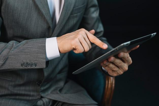La mano dell'uomo d'affari che tocca lo schermo digitale della compressa con il dito