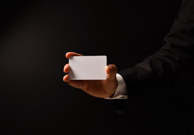 La mano dell'uomo d'affari con biglietto da visita in bianco