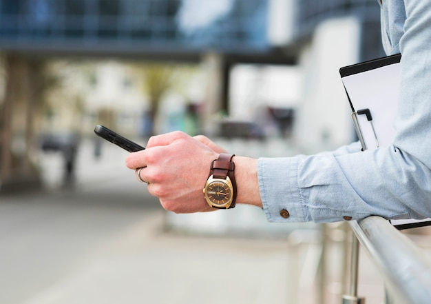 La mano dell'uomo d'affari con l'orologio da polso elegante che per mezzo del telefono cellulare