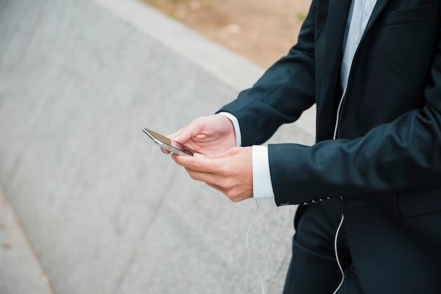 La mano dell'uomo d'affari facendo uso del telefono cellulare