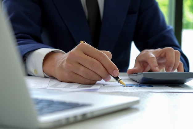 La mano dell'uomo d'affari lavora ad un calcolatore e usa una penna che indica al grafico.