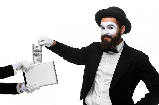 La mano dell'uomo d'affari sotto forma di soldi dell'estratto del mimo dal pc della compressa