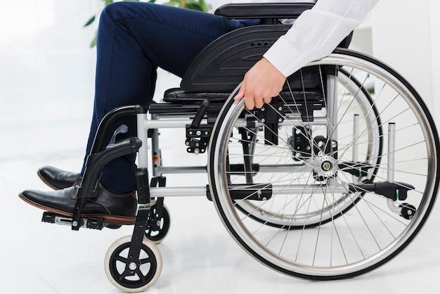 La mano dell'uomo d'affari sulla ruota che si siede sulla sedia a rotelle