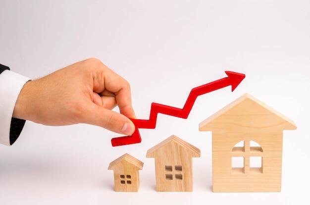 La mano dell'uomo d'affari tiene la freccia rossa su sopra le case. crescita della domanda