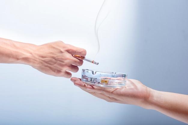 La mano dell'uomo dà un posacenere trasparente al fumatore