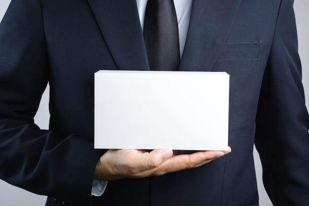 La mano dell'uomo di affari che tiene la scatola bianca in bianco dà il regalo