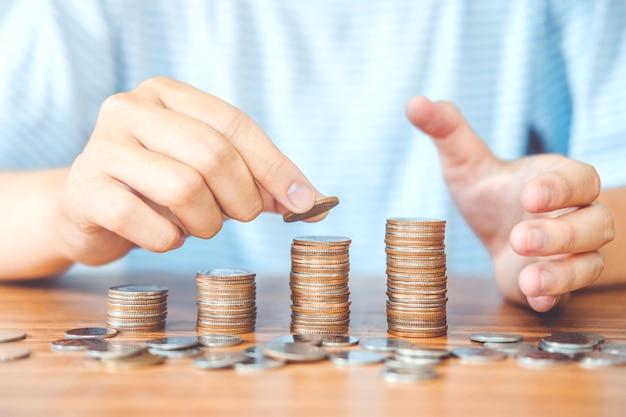 La mano dell'uomo di concetto dei soldi di risparmio che mette la finanza della pila della moneta per il bilancio