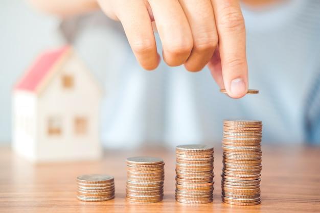 La mano dell'uomo di concetto dei soldi di risparmio che mette la finanza della pila della moneta