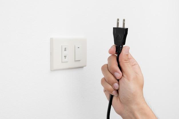 La mano dell'uomo disinserisce la spina di presa elettrica sul concetto bianco di sicurezza del fondo della parete