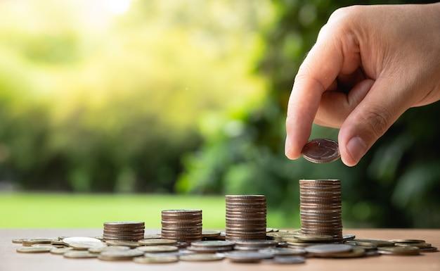 La mano dell'uomo ha messo le monete dei soldi alla pila di monete