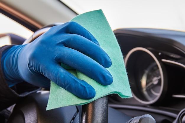 La mano dell'uomo in guanto protettivo blu sta pulendo il volante con un panno. disinfezione durante la protezione da coronavirus o covid-19.