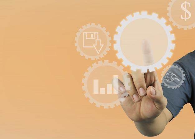 La mano dell'uomo indica l'ingranaggio circolare vuoto sul fondo arancio di colore.