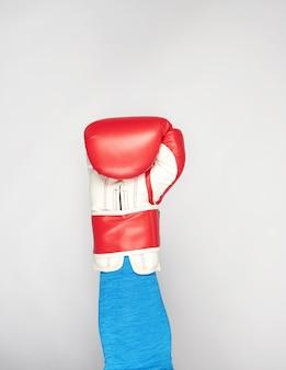 La mano dell'uomo indossa un guantone da boxe in pelle rossa