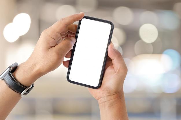 La mano dell'uomo mostra smartphone mobile con schermo bianco su sfondo sfocato.