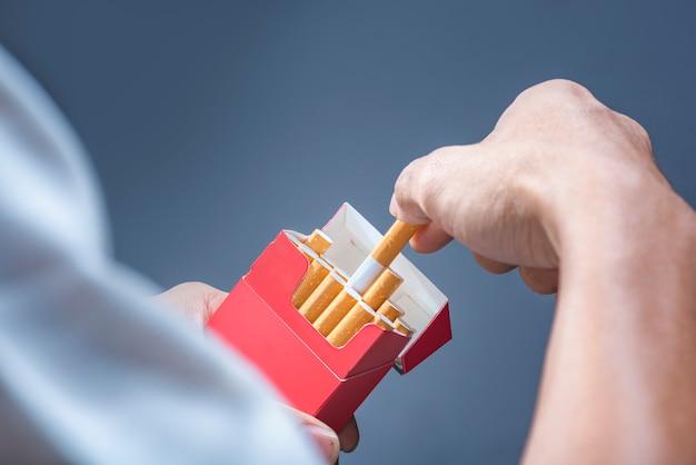 La mano dell'uomo prende una sigaretta dal pacchetto di sigarette rosso