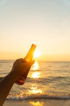La mano dell'uomo sta tenendo la bottiglia di birra e tiene la sua mano sul cielo in serata con il tramonto.