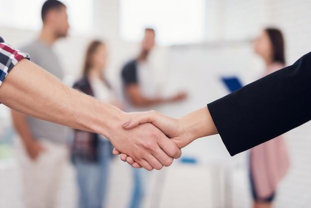 La mano dell'uomo stringe la mano della donna con la compagnia
