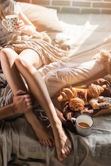 La mano dell'uomo sulla gamba della donna che si siede sul letto con la prima colazione al forno e la tazza di caffè