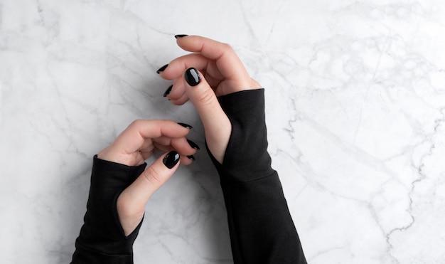 La mano della bella donna con il manicure elegante su fondo di marmo