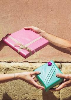 La mano della coppia che dà il regalo del biglietto di s. valentino l'un l'altro davanti alla parete