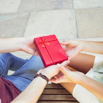 La mano della coppia che tiene il contenitore di regalo rosso