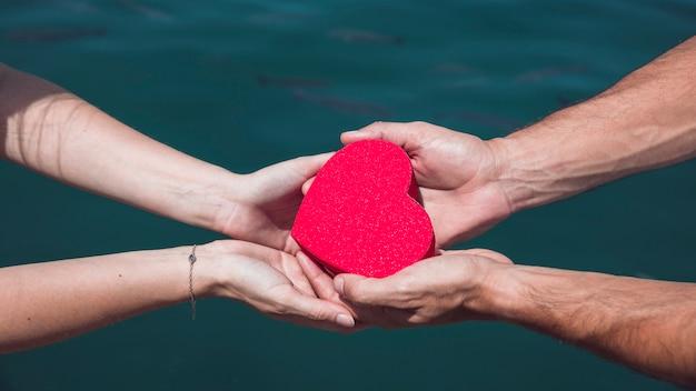 La mano della coppia che tiene la forma rossa del cuore contro il fondo dell'acqua di mare