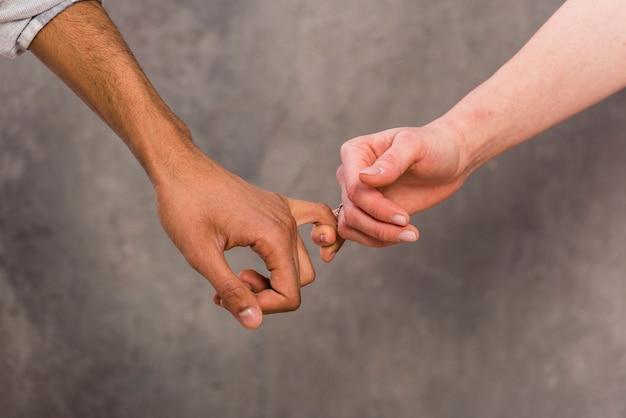La mano della coppia interrazziale che tiene il dito di ciascuno contro il contesto concreto