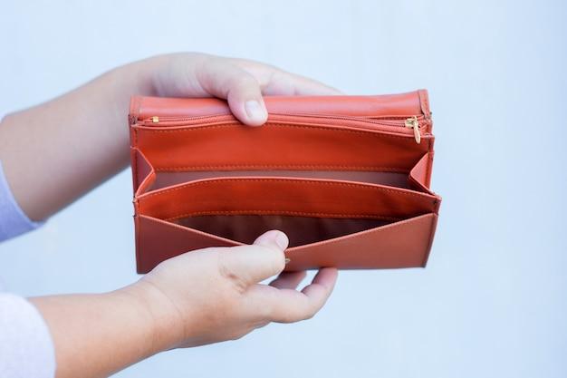 La mano della donna apre un portafoglio vuoto