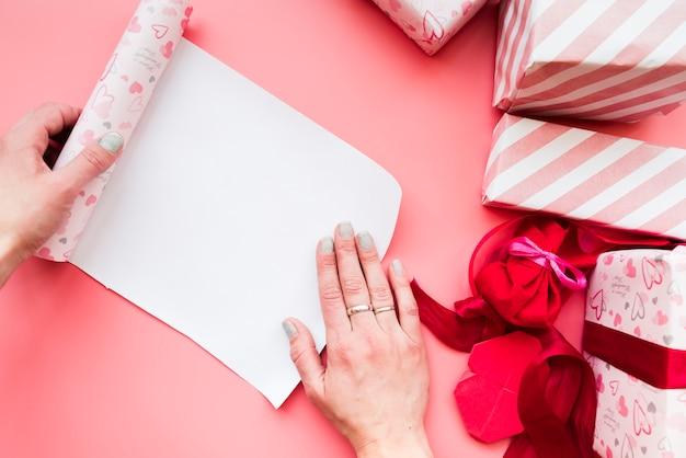 La mano della donna che apre la carta accartocciata del regalo con il contenitore di regalo avvolto su fondo rosa