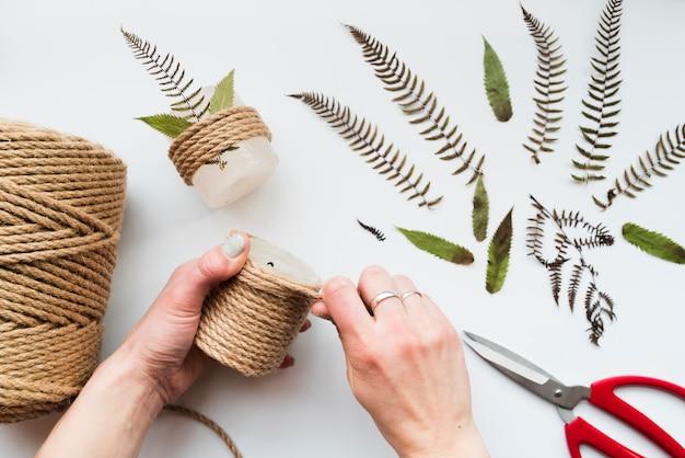 La mano della donna che avvolge la corda sulla candela con le foglie e le forbici su fondo bianco