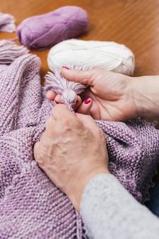 La mano della donna che fa la nappa di lana