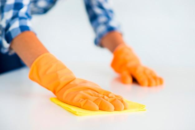 La mano della donna che indossa un guanti arancioni pulisce la scrivania bianca con uno spolverino giallo