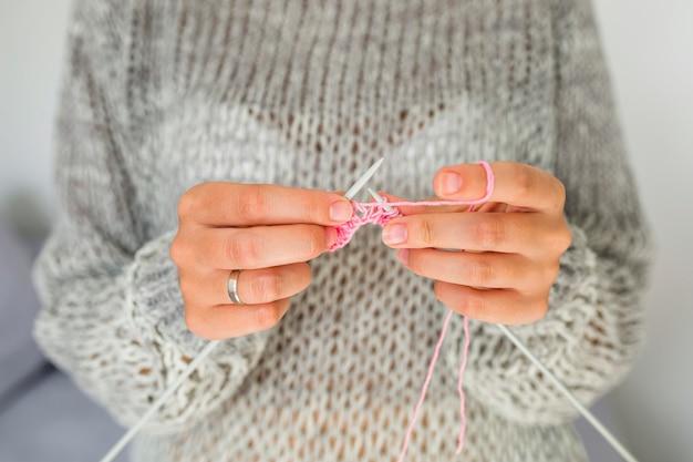 La mano della donna che lavora a maglia con l'uncinetto