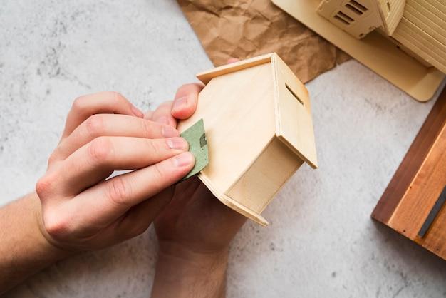 La mano della donna che liscia la casa di legno del porcellino salvadanaio