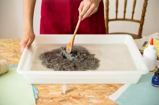La mano della donna che mescola la polpa di carta in acqua