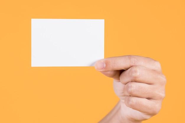 La mano della donna che mostra il biglietto da visita bianco in bianco contro il fondo giallo