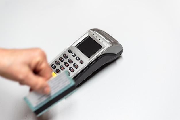 La mano della donna che passa la carta di credito da un dataphone, lettore di schede per caricare in tempo di vendite.