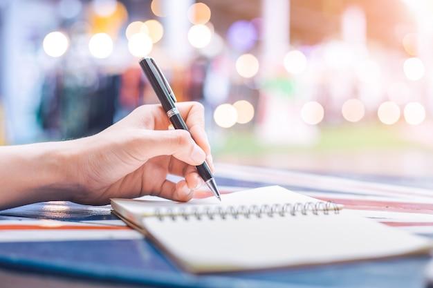 La mano della donna che scrive su un taccuino con una penna su una scrivania in legno.