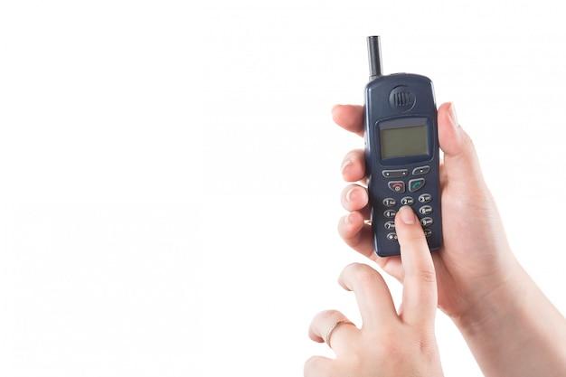 La mano della donna che tiene il vecchio telefono cellulare e preme i bottoni isolati su bianco