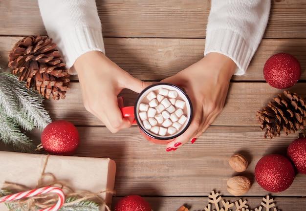La mano della donna che tiene la tazza rossa di cacao di natale con caramelle gommosa e molle.