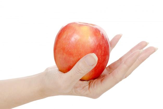 La mano della donna che tiene mela rossa. isolato su uno sfondo bianco.